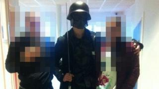 This picture made available to AFP by a student shows the masked man armed with a sword posing for a photo with two other students before attacking students and staff in Trollhattan, southwestern Sweden, on October 22, 2015.