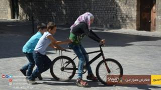Syrian children play with a bike