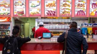 Customers wait to be served at a fast food takeaway
