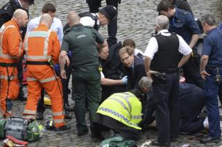 Conservative Member of Parliament Tobias Ellwood, centre, helps emergency services attend to an injured policeman outside the Houses of Parliament, London.