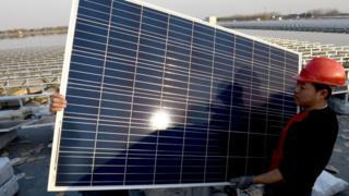 Trabajadores chinos instalan un panel solar en una planta fotovoltáica en la provincia de Huainan