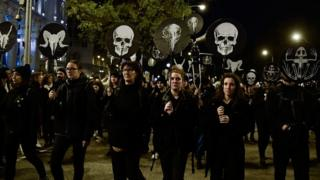 Demonstrators hold skull masks during a mass climate march