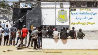 مهاجرون افارقة أمام مركز إيواء تاجوراء
