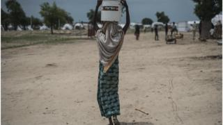 Woman wey carry water for head