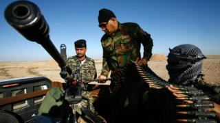 "Iraqi soldiers check their weapons as they are stationed on the Iraqi-Saudi border in Iraq""s southern Samawah"