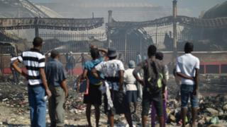 Citizens look as the burnt hull of the Iron Market.