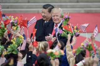 米中の旗を振る子供たちに出迎えられたトランプ氏と習氏(9日、北京・人民大会堂前)