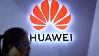 Logo de Huawei con mujer desenfocada en primer plano.