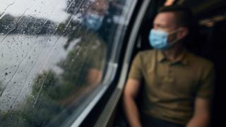 A man in a mask looking through a rainy train window