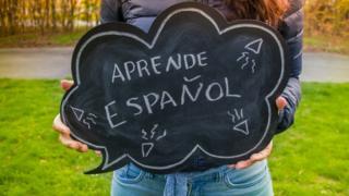 """Una mujer sostiene un cartel que dice """"Aprende español"""""""