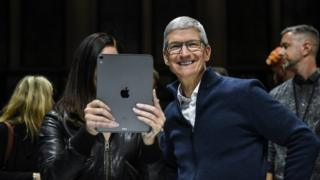 Tim Cook, CEO of Apple laughs while Lana Del Rey (with iPad) takes a photo during a launch event at the Brooklyn Academy of Music on October 30, 2018 in New York City. Apple debuted a new MacBook Pro, Mac Mini and iPad Pro.