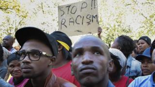 """Protesters in South Africa hold up a """"stop racism"""" sign"""