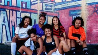 Шесть девушек-футболисток на фоне исписанных графити стен футбольной площадки