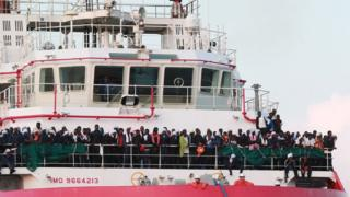 Migrants arrive on a rescue ship in Italy on 14 July