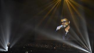 Chris Martin on stage with George Michael on a video screen