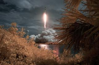 A SpaceX Falcon 9 rocket carrying the Crew Dragon spacecraft launches in the distance