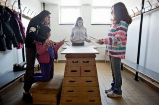 A group of girls practice drumming on wood