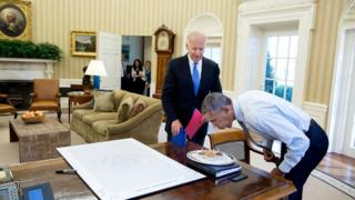 "Mr Obama blows out candles as Joe Biden stands over him in the White House. Some West Wing staff members can be seen in the distant doorway, and a large framed piece of text titled ""all the president's notions"" lies on the desk."