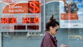 Una mujer pasa frente a un banco que muestra el cambio del rublo