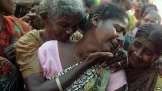 An Indian woman breaks down as she sees the dead body of her family member, a victim of toxic home-made liquor consumption, in Mumbai on 20 June 2015.