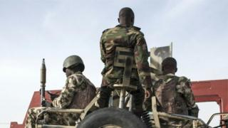 Nigerian soldiers with weapon on top vehicle