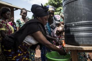 Congolese women are seen washing their hands at a chlorinated hand washing point in Mangina