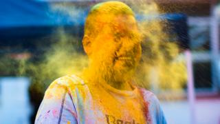 in_pictures A person with yellow powder on their face in Durban, South Africa - Monday 9 March 2020