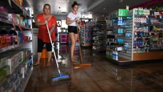 Two women sweep water away inside a store.