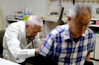 Ryuichi Nagayama examines a patient