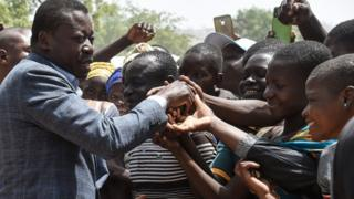 Faure Gnassingbé (L) shakes hands with supporters during his visit to a military hospital at Namoundjoga village in northern Togo, on February 17, 2020.