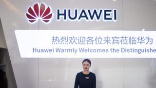 A hostess waits as journalists arrive for a press conference and launch of new 5G Huawei products at the Huawei Beijing Executive Briefing Centre