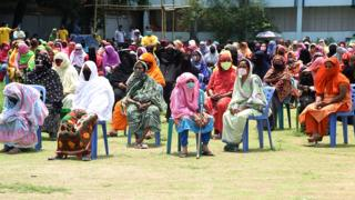 Women in Bangladesh wait to receive relief material during government imposed lockdown