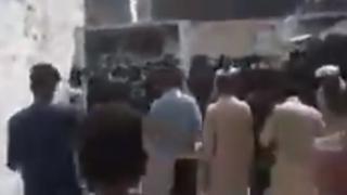A still from a video showing men walking down a street