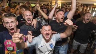 Fans celebrate inside a Manchester pub