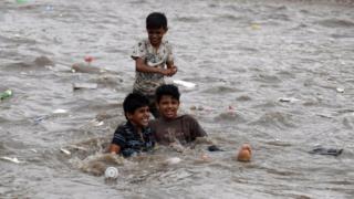 Yemeni boys enjoy rainwater at a flooded street following heavy rainfall in the old quarter of Sanaa