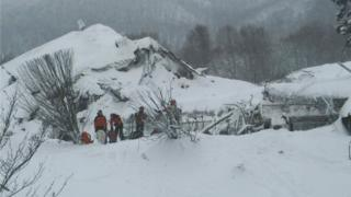 Members of Lazio's Alpine and Speleological Rescue Team stand in front of the Hotel Rigopiano in Farindola, central Italy