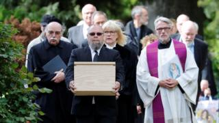 Mourners with coffin containing victims' tissue, 13 May 19