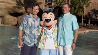 Left to right: Tom Staggs, Mickey Mouse and Bob Iger