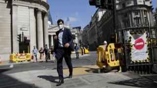 A man wearing a face mask as a precaution against the transmission of the novel coronavirus walks near the Royal Exchange and the Bank of England in the City of London on July 17, 2020.