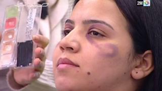 Foto del video en el que una mujer luce un moretón ficticio y que es maquillada para ocultarlo.