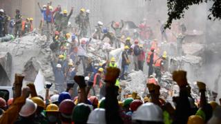 Rescuers raise their fists for silence at the site of a collapsed building in Mexico City