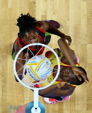 Two Netball players stand next to the net, watching the ball go in. They are both reaching upwards and looking intently at the ball.