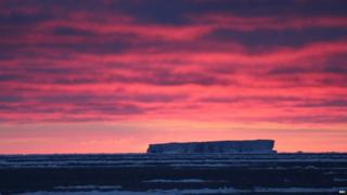 A bright pink and red sky, over a large iceberg