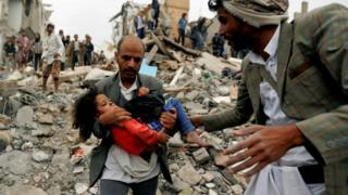 A man carries a girl from the site of a Saudi-led coalition air strike in Sanaa, Yemen (25 August 2017)