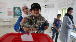 A woman has a child cast her ballot for her