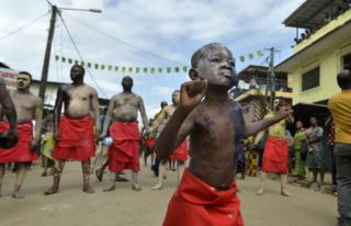A young boy wearing a red wrap and smatterings of face and body paint dances ahead of a line of older men who are dressed in the same way.