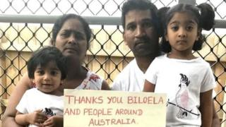"A family picture of Nadesalingam and Priya and their two daughters holding a sign reading ""thanks you Biloela and people around Australia"""