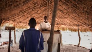A man and a priest in Southern Sudan stood inside a hut at the refugee camp of Obo The man has his back turned facing the priest as he conducts mass.