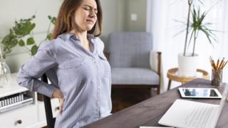 Mujer trabajando desde casa con dolor de espalda.