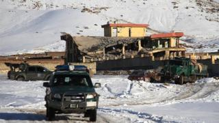 An Afghan military vehicle is seen near a site after a car bomb attack on a military base in the central province of Wardak on January 21, 2019.
